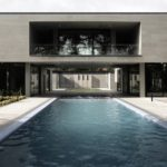 Elevated walkway bridges two parts of home divided by swimming pool